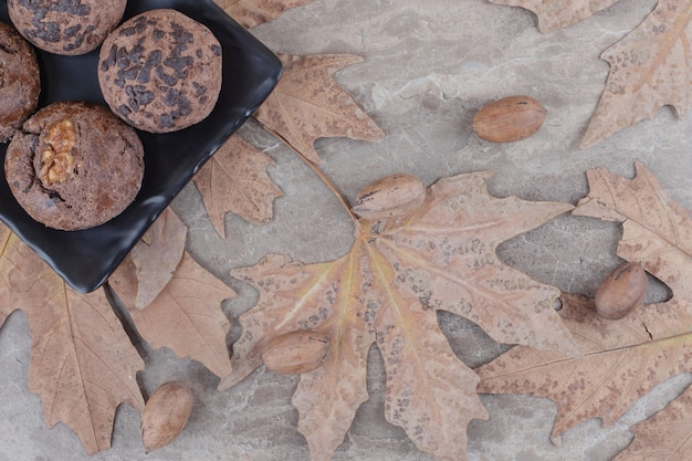 Cookies on a platter next to scattered plane tree leaves and pecan nuts on marble