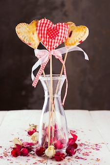 Cookies pops in the form of heart and heart from fabric in a pattern a red cage with buds of roses