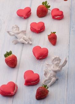 バレンタインデーの木の板に赤いハート型のイチゴと天使のクッキー
