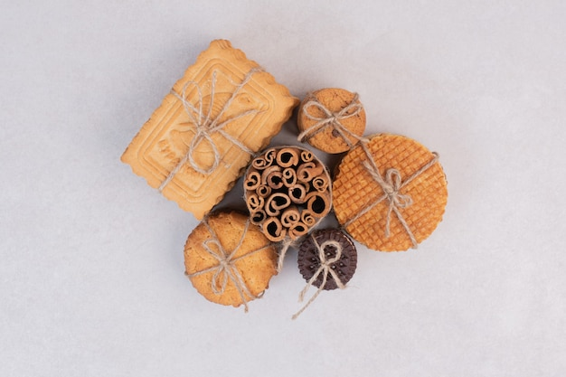 Cookies in rope with cinnamon sticks on white surface