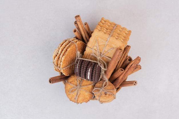 Biscotti in corda con bastoncini di cannella sulla superficie bianca