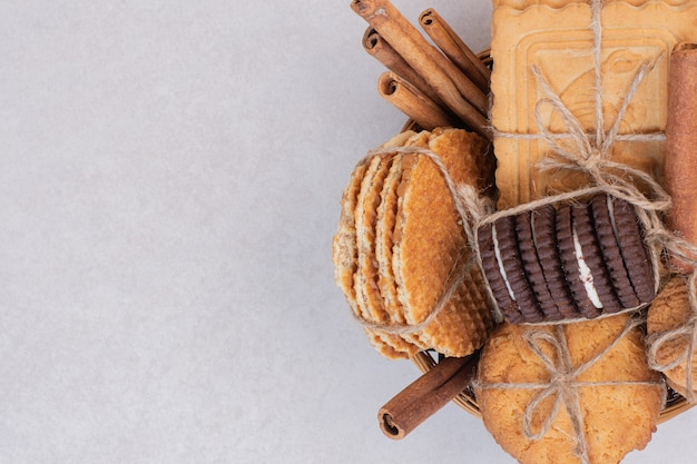 Cookies in rope with cinnamon on white surface