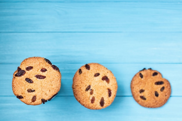 Cookies in a row on blue wall. selective focus