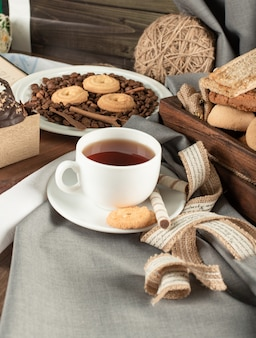 Cookies in rustic trays and a white cup of tea on a rustic table