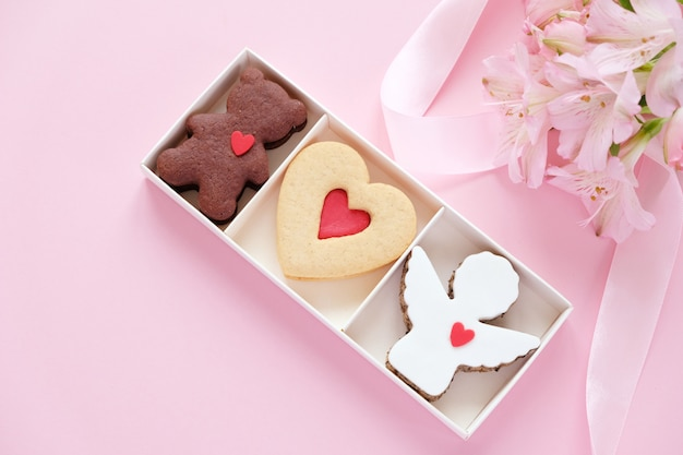 Cookies in the shape of an angel, a heart, a bear with a pink ribbon with lisianthuses