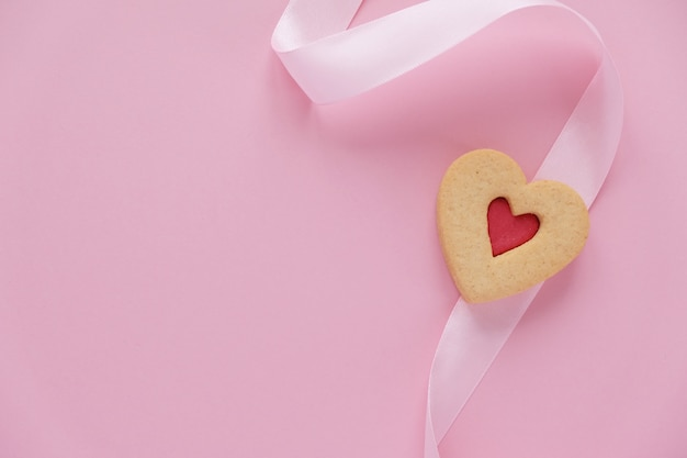 Cookies in the shape of a heart with a pink ribbon on pink