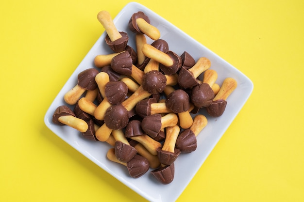 Cookies in the shape of a mushroom, the chocolate hat and leg of the test. sweet dessert for children chocolate mushroom. yellow background. copy space.