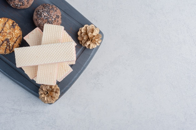 Cookies next to a stack of wafers on a navy board with pine cones on marble surface