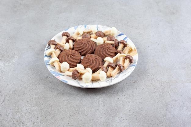 大理石の背景のプレートにチョコレートのキノコに囲まれたクッキー。高品質の写真