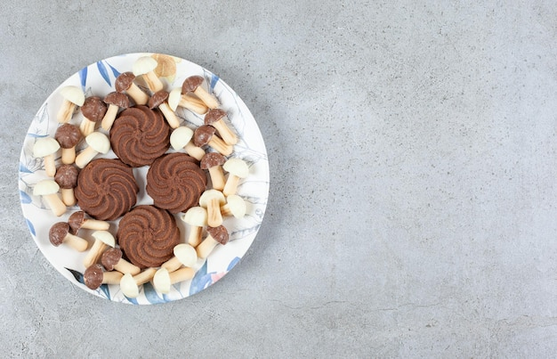 大理石の背景のプレートにチョコレートのキノコに囲まれたクッキー。