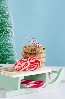 Cookies and sweets of christmas on wooden sled with tree