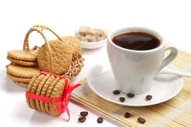 赤いリボンと一杯のコーヒーで結ばれたクッキー