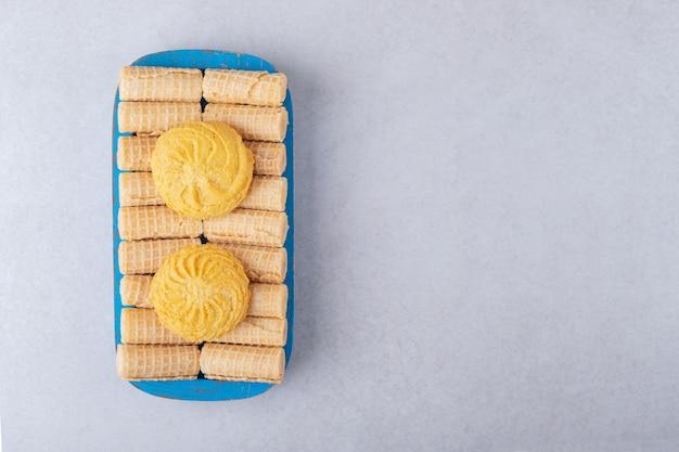 Biscotti su rotoli di cialda sul vassoio di legno, il marmo.