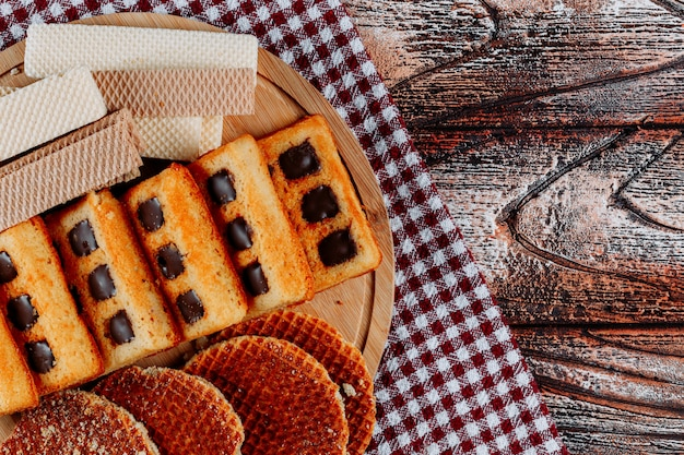 Cookies and waffles on a cutting board top view on a cloth and wooden background