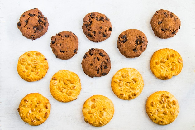 Cookies on white table, sweet pastry dessert with chocolate and nuts, top view