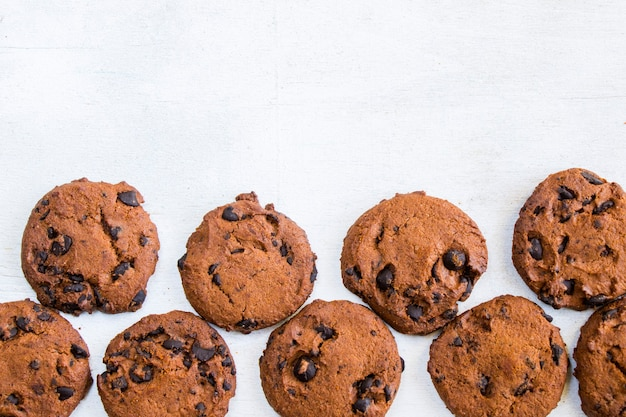 Cookies on white wooden table, top view
