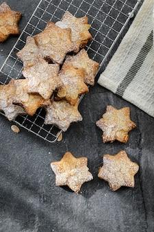 Печенье с миндалем и сахарной пудрой с бежевой салфеткой на темном бетоне