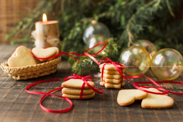 Cookies with baubles on wooden table