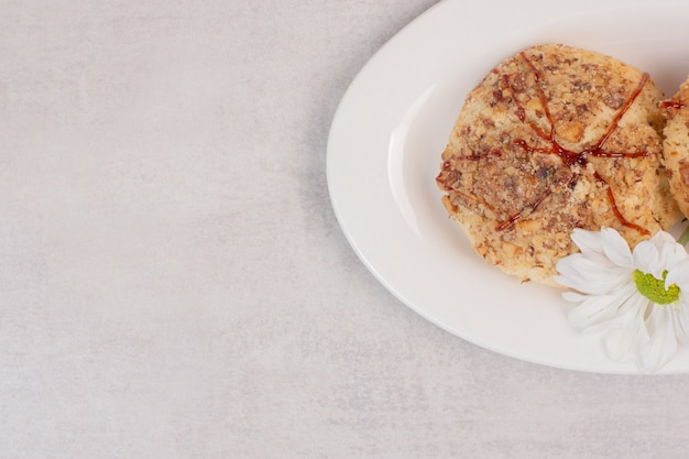 Biscotti con salsa al caramello e fiore su bianco.