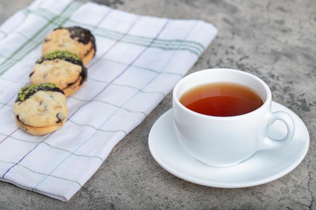 Печенье с шоколадом и чашкой черного чая на каменном фоне.
