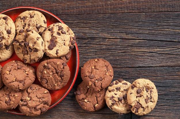 어두운 나무 배경에 빨간색 접시에 초콜릿과 견과류가 있는 쿠키, 위쪽