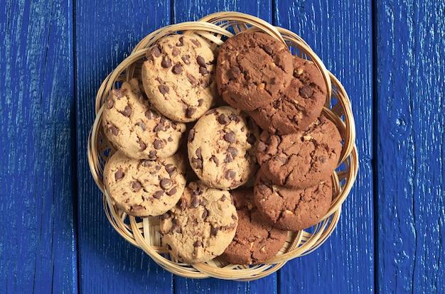 푸른 나무 배경의 고리버들 접시에 초콜릿과 견과류를 넣은 쿠키, 위쪽