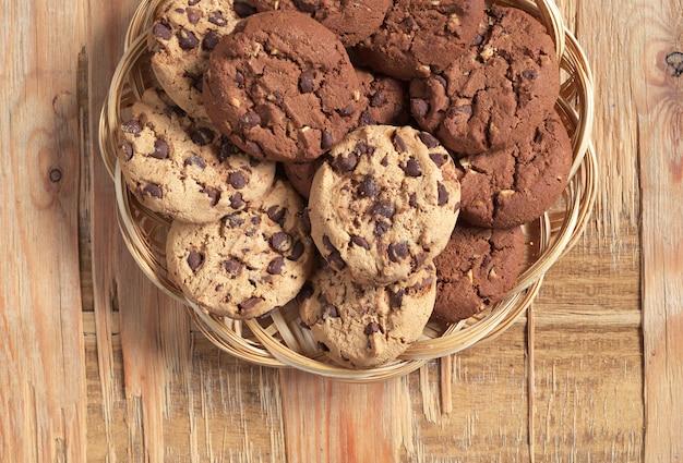 오래된 나무 배경에 있는 고리버들 접시에 초콜릿과 견과류를 넣은 쿠키, 위쪽