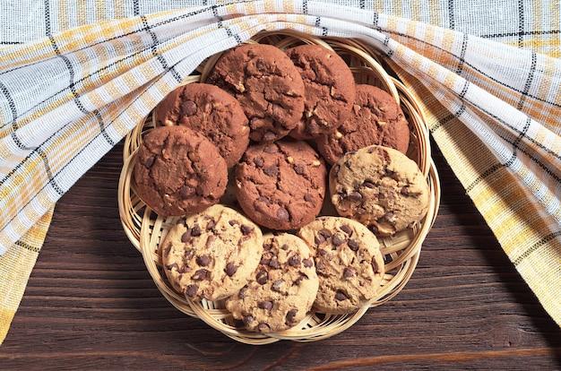 소박한 나무 테이블에 있는 고리버들 접시에 초콜릿과 견과류를 넣은 쿠키, 위쪽 전망