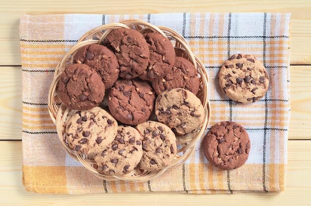 나무 테이블에 있는 고리버들 접시에 초콜릿과 견과류를 넣은 쿠키, 위쪽