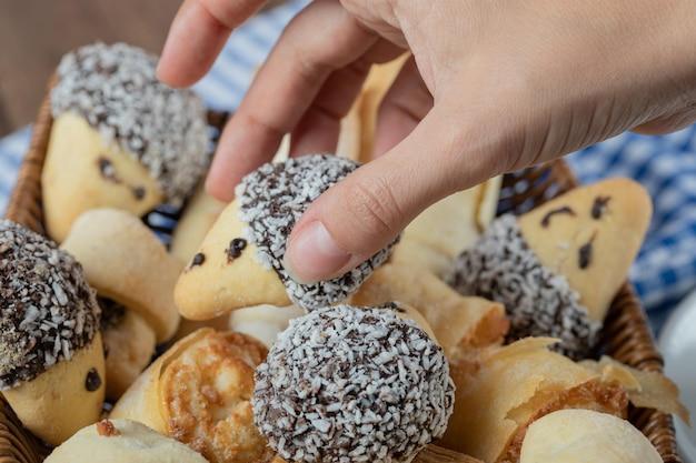 Biscotti con cioccolato e cocco tritato su cesto di legno.