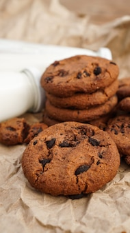 クラフト紙とミルクのボトルにチョコレートのドロップが付いたクッキー。健康的な朝食のための天然の手作り有機ヘビ。縦の写真