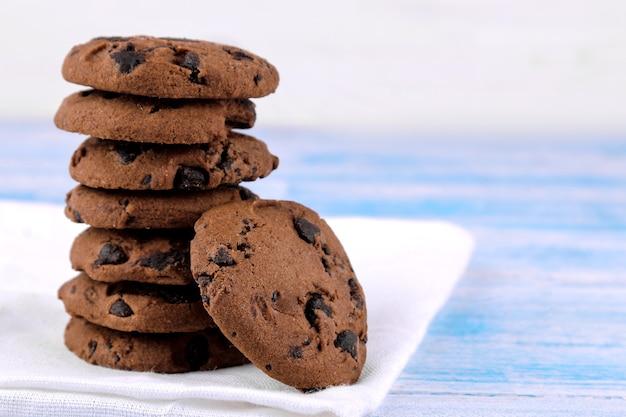 青い木製のテーブルの上の白いナプキンの上に山積みに折りたたまれたチョコレートとクッキー。焼く。うまい。