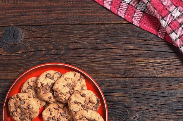 어두운 나무 테이블에 빨간 접시에 초콜릿이 있는 쿠키, 위쪽
