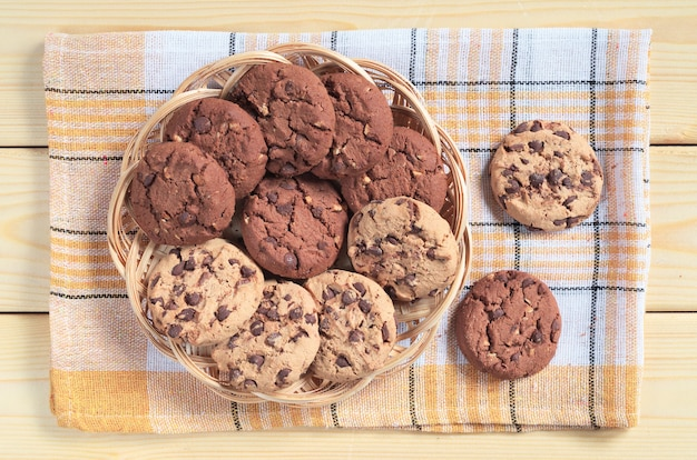 Cookies with chocolate and nuts in wicker plate on wooden table, top view