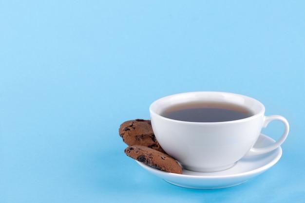 明るい青色の背景に一杯のコーヒーとプレート上のチョコレートとクッキー。ベーキング。うまい
