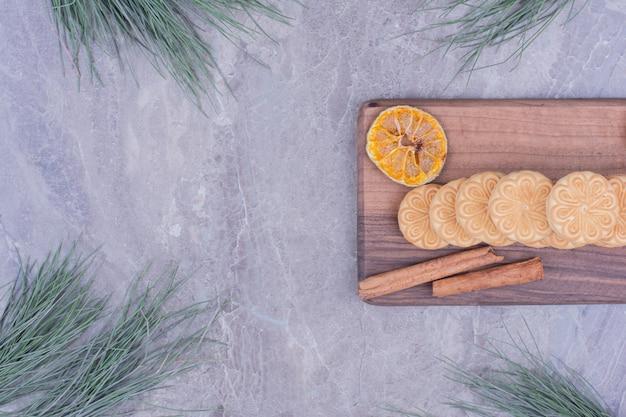 木の板にシナモンスティックとドライレモンスライスのクッキー