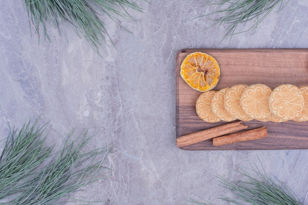 Cookies with cinnamon sticks and dry lemon slices on a wooden board