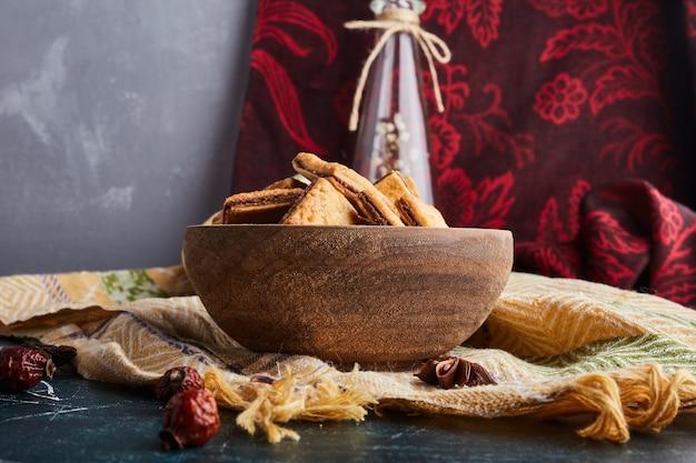 Печенье с начинкой какао в деревянной чашке.