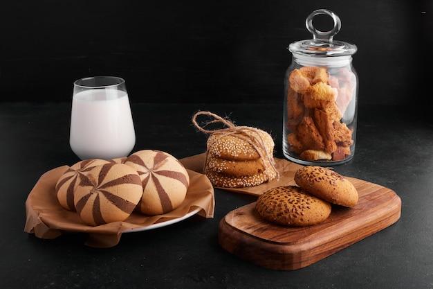 黒の背景に牛乳のガラスとココア、ゴマ、クミンのクッキー。