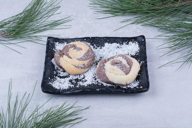 검정 잉크 판에 코코넛 가루와 쿠키.