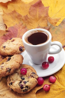 Cookies with cranberries and cup of coffee on autumn leaves