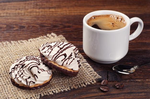 Печенье со сливочным шоколадом и кофейной чашкой на старом деревянном столе