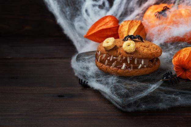 ハロウィーンのお祝いのためのモンスターの形をしたクリームペースト入りのクッキー。オートミールクッキーと練乳で作った面白い自家製の顔。コピースペース
