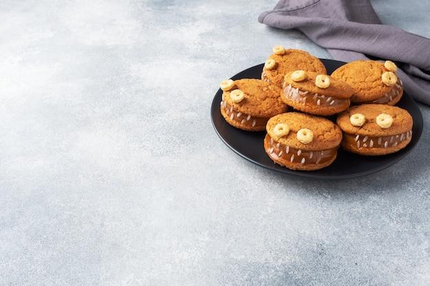 ハロウィーンのお祝いのためのモンスターの形をしたクリームペースト入りのクッキー。オートミールクッキーとコンデンスミルクで作った面白い自家製の顔。コピースペース
