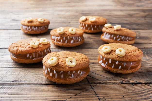 ハロウィーンのお祝いのためのモンスターの形をしたクリームペースト入りのクッキー。オートミールクッキーと練乳で作った面白い自家製の顔。
