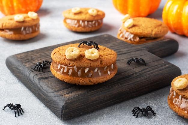 ハロウィーンのお祝いのためのモンスターの形をしたクリームペースト入りのクッキー。オートミールクッキーとコンデンスミルクで作った面白い自家製の顔。