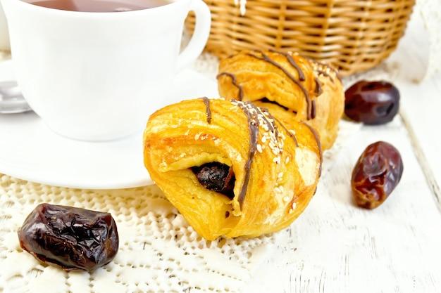 日付の入ったクッキー、木の板を背景にナプキンのカップにお茶