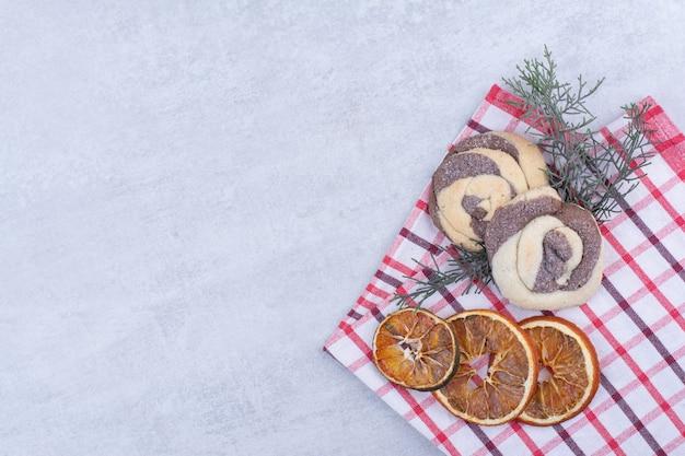 Biscotti con arancia secca su tovaglia e ramo di pino.