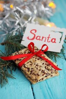 아마씨와 해바라기가 들어간 쿠키와 산타라고 적힌 카드. 푸른 나무 테이블에 선물