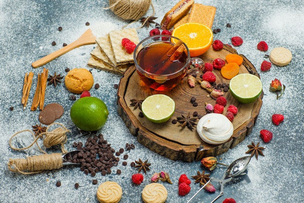 Cookies with flour, tea, fruits, spices, choco, strainer flat lay on wooden board and stucco background